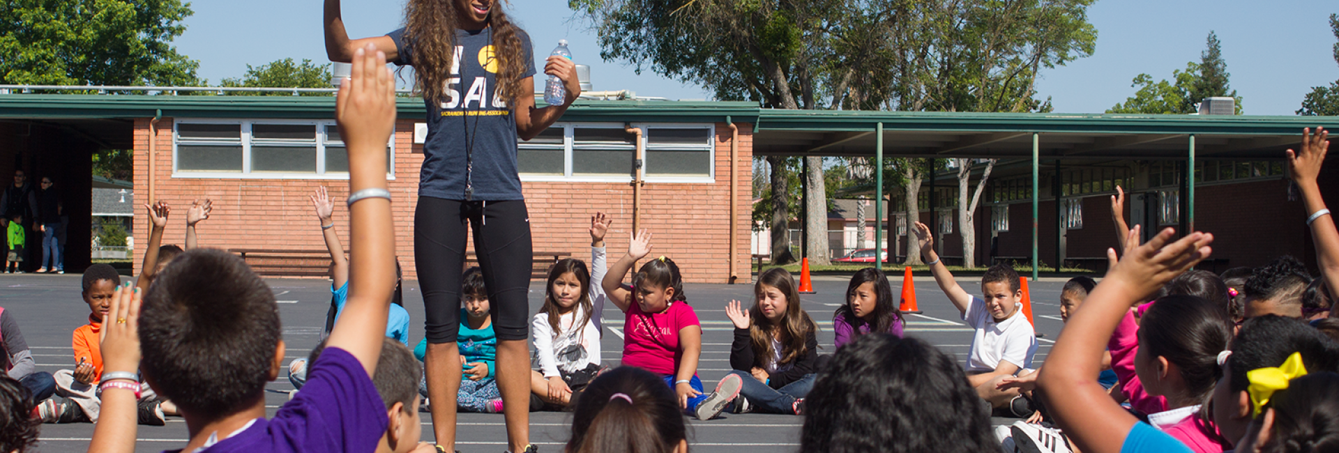 Image of Runner Lea Wallace motivates Edward Kemble, Cesar Chavez students
