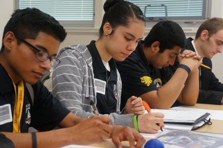 Students take notes at conference.
