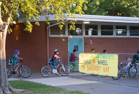 Bancroft kids wheel their bikes onto campus