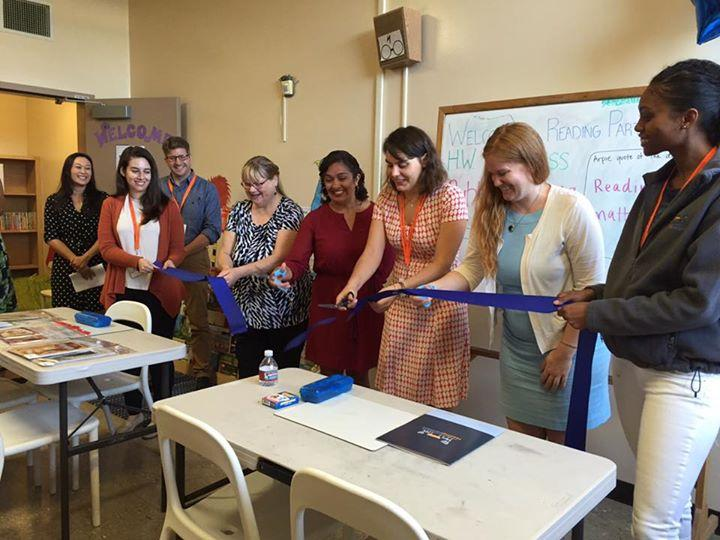 Site Coordinator Julia Glick of Reading Partners cuts the ribbon on a new Literacy Center at Harkness Elementary School.