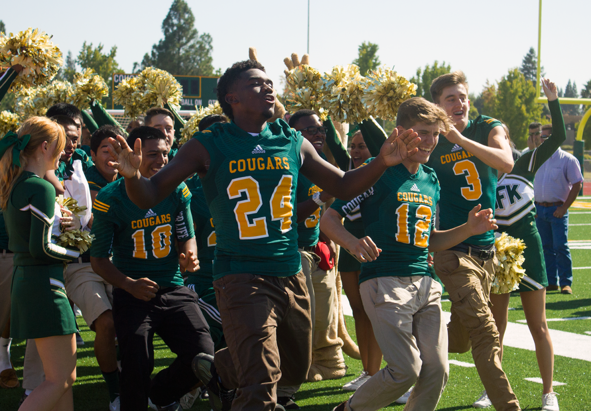 JFK students celebrate their new track and field at a ribbon-cutting last week.