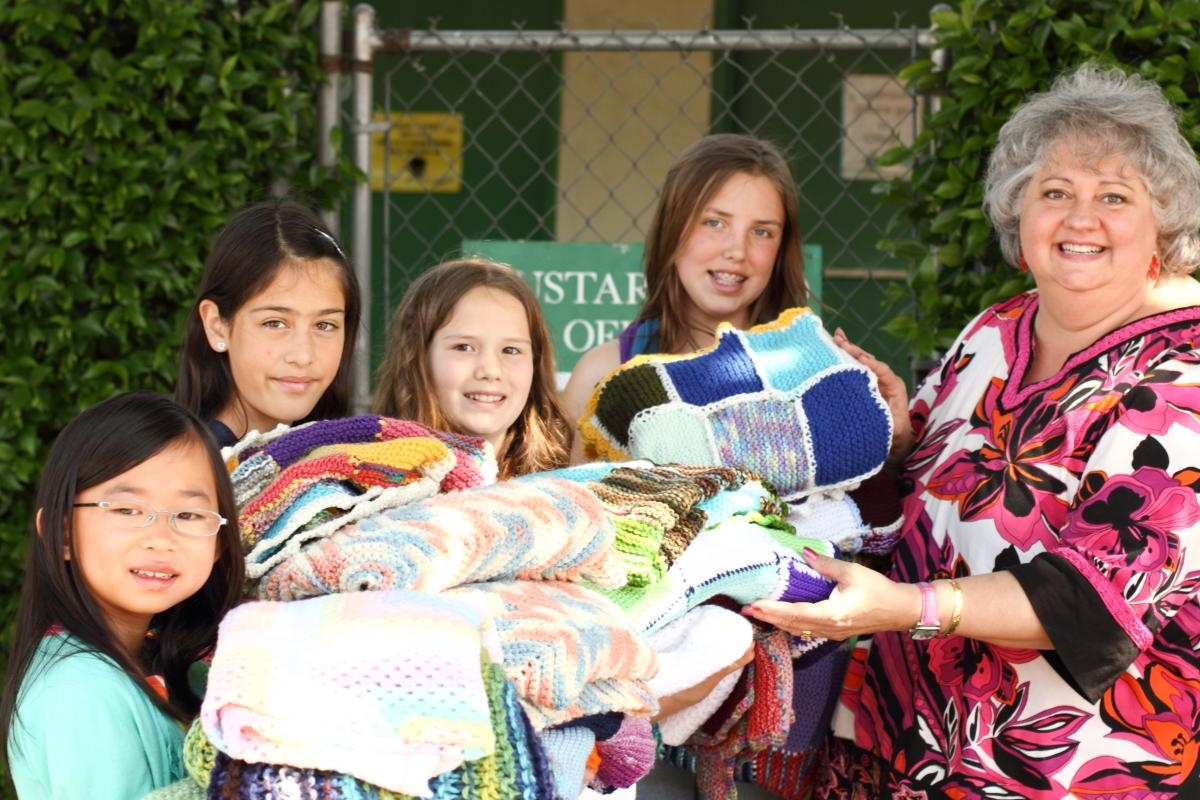 Knitting champs Mei Van Eskeridge, April Crespo, Emma Bath and Payton Herzog deliver blankets to Miss Yvonne from Project Linus.