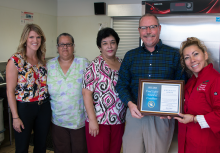 John Sloat's cafeteria team was honored by Sacramento County Supervisor Patrick Kennedy (holding plaque)
