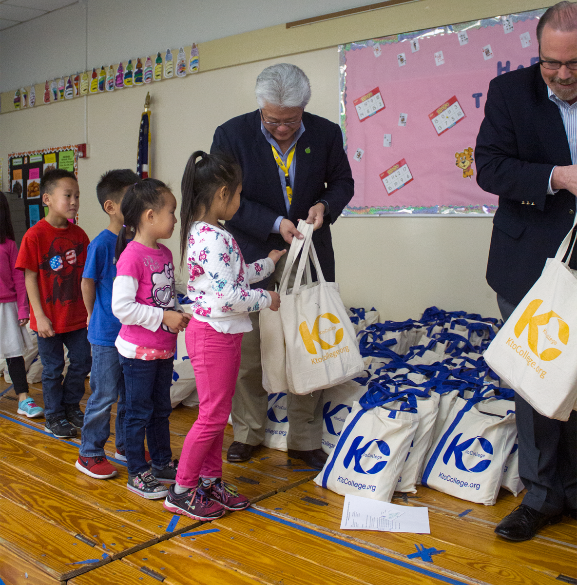 SCUSD Board of Education President Darrel Woo and Sacramento County Supervisor Patrick Kennedy help hand out bags to students
