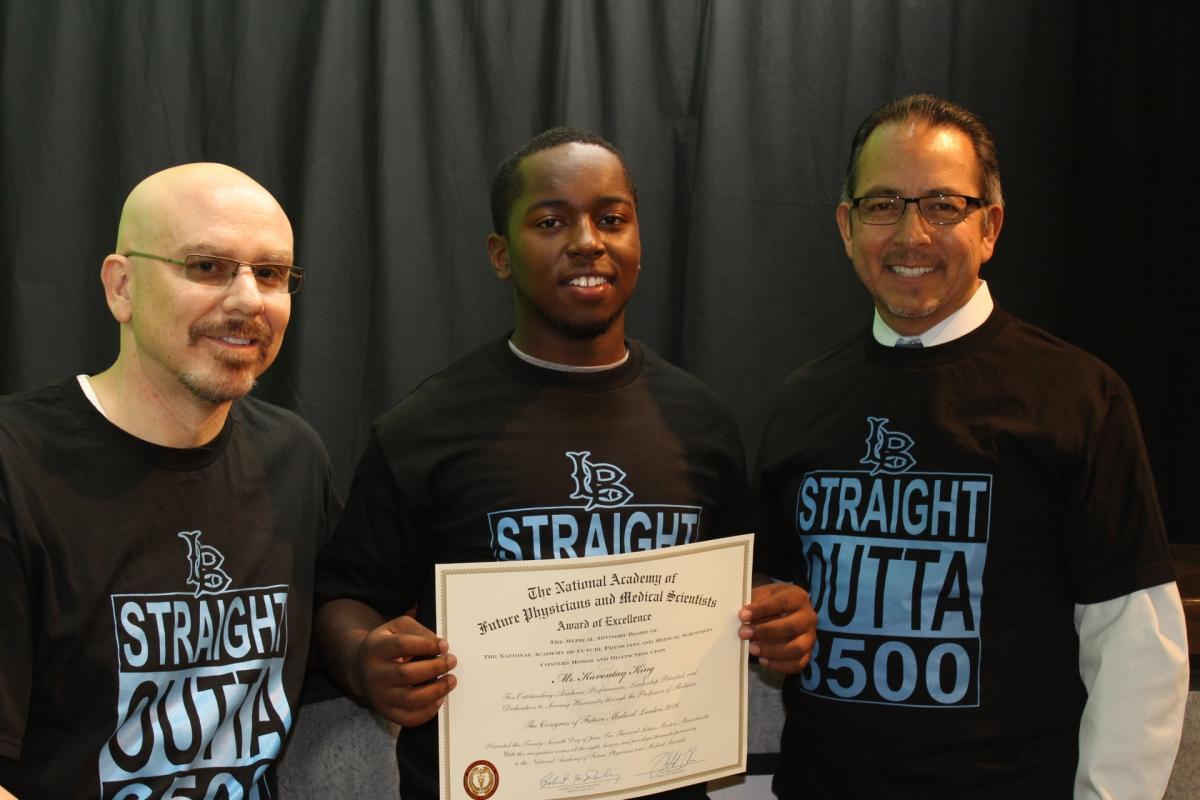 Burbank Principal Jim Peterson and Superintendent José L. Banda present a certificate to Kevontay King