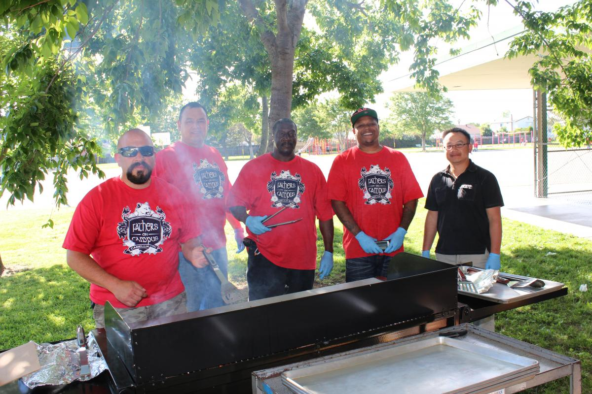 Image of Camellia's Fathers on Campus man the barbecue at Open House