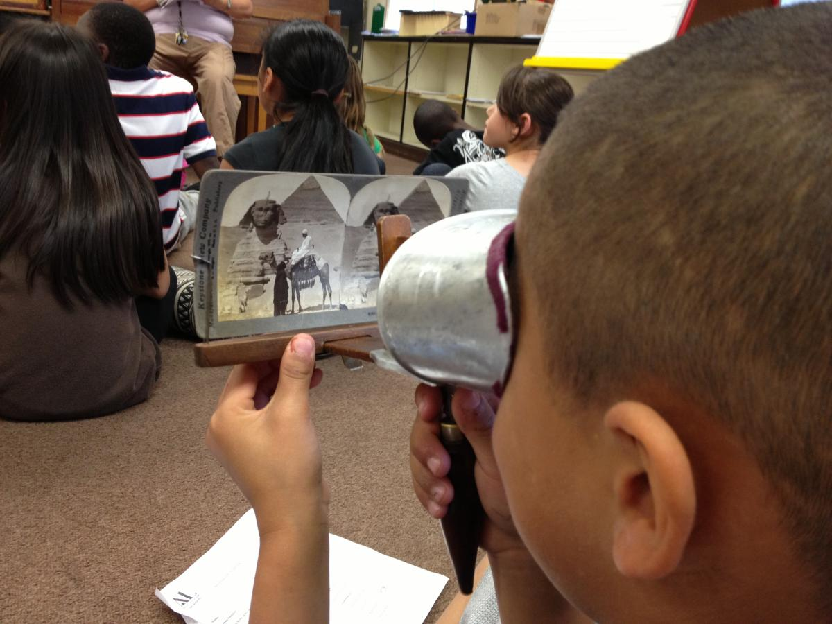 A John Sloat student studies an old photograph using a stereoscope.
